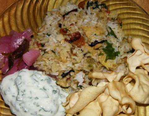 chicken biryani with pickled onion, spinach raita, and papad